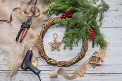 Top view of stages of making Christmas wreath with fir branches and decorative toys on wooden rustic tabletop. Toned royalty free stock photo