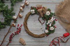 Top view of stages of making Christmas wreath with fir branches and decorative toys on wooden rustic tabletop. Toned royalty free stock photography