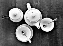 Top view of the stages of preparing a cup of hot tea. A white empty cup, black tea, sugar with them, hot water. Flat laying of cups with ingredients on a brown royalty free stock image