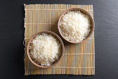 Top view: steamed cooked basmati rice in round ceramic bowls over black stone Royalty Free Stock Photo