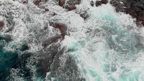 Top view. Steep volcanic shore, reefs of frozen volcanic lava, stormy ocean, white foam from the giant waves that hit stock video footage
