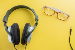 Stereo Headphones and Spectacles on Yellow background. Top view of Stereo Headphones and Spectacles Placed on the left of the image with space for text. the royalty free stock images