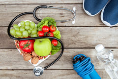 Top view of stethoscope, organic vegetables and fruits and sport equipment on wooden surface. Healthy lifestyle concept Stock Photo