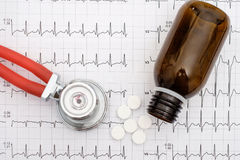 Top view of stethoscope and pills on an electrocardiogram Stock Photo