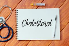 Top view of stethoscope,syringe,pen and notebook written with Cholesterol on wooden background, Health concept. Top view of stethoscope,syringe,pen and notebook royalty free stock photography