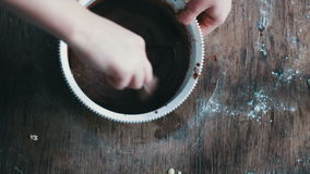 Top view stirring chocolate cookie dough with a spoon in a white plastic bowl stock video footage