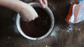 Top view stirring chocolate cookie dough with a spoon in a white plastic bowl stock video