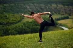 Top view on stone, athlete young man with naked torso in sportswear doing stretching exercises, landscape background. stock images