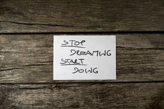 Top view of a Stop dreaming start doing message Stock Image