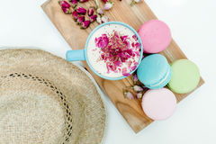 Top view on straw hat and blue cup of aroma cappuccino with french tasty macarons cookies. Top view on straw hat and blue cup of aroma cappuccino with french Royalty Free Stock Image