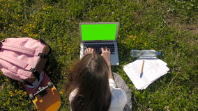 Top View of a Student Using Laptop With Green Screen While Lying On The Grass. 4K stock video footage