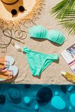Top view of stylish blue bikini with various accessories and magazine. On sandy beach stock photo