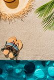 Top view of stylish flip flops and straw hat. On sandy beach royalty free stock photography
