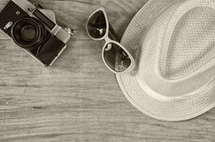 Top view of stylish hat woman sunglasses old camera over wooden table. black and white photo. vacation and travel concept Royalty Free Stock Photo