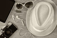 Top view of stylish hat woman sunglasses old camera and tablet device over wooden table. black and white photo. vacation and trave Royalty Free Stock Photos