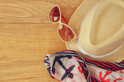 Top view of stylish hat woman sunglasses and tablet fashion nautical scarf over wooden table. vacation and travel concept Royalty Free Stock Image