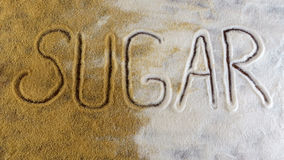 Top view of sugar inscription on white and brown sugary grain Stock Photo