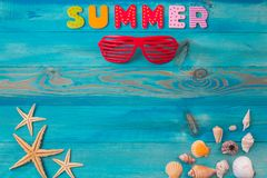 Top view summer holidays background concept with louvered shades, seashells and sea starfish on blue wooden table stock photos