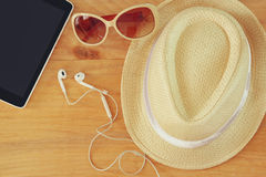 Top view of sunglasses, hat tablet device and earphones over wooden table Stock Image
