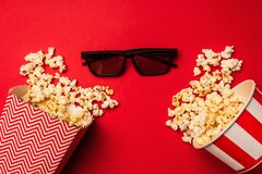Top view of sunglasses near buckets with popcorn
