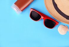 Top view of sunglasses, shells, starfish, sunblock and hat Stock Photos