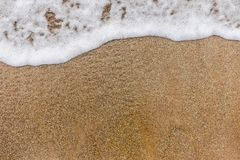 Top view of surface of clean golden sand at sea beach and white foamy wave. Horizontal color photography royalty free stock photo