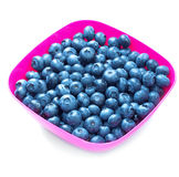 A top view of sweet juicy blueberries in a bright pink plastic bowl, isolated on a white background. Berries full of vitamins. A close-up of nutritious Stock Photo