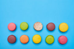 Top view of sweet macarons with copy space over blue flatlay. Two lines of colourful macaroons stock photo