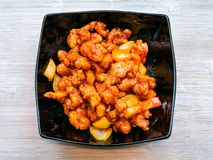 Top view of Sweet and Sour Chicken on gray table. Chinese cuisine dish - top view of black bowl with Fried chicken pieces with pineapple and bell pepper and stock image