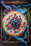 Top view of sweet tart made of berries and mascarpone. On old wooden table stock image