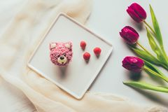 Top view of sweet tasty muffin in shape of bear, fresh raspberries and tulip flowers Royalty Free Stock Image