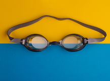 Swimming goggles on blue and yellow background. Top view of swimming goggles on blue and yellow background paper Royalty Free Stock Image
