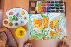 Top view on table behind which painted watercolor on paper goldfish Stock Images