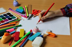 Top view on table with blank sheet of paper and baby`s hand with pencil. Back to school. Color paints with paint brushes, pencils royalty free stock images