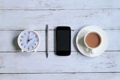 Top view of table clock,pen,smartphone and a cup of coffee on white wooden background Stock Photo