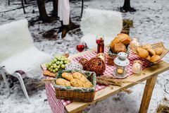 Top view of a table with dread and cookies baskets. And candles, two chairs covered with white fur on the background. Picnic in the winter forest Stock Photo