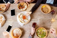 Top view on the table full of asian meals. Top view on the table full of different asian meals served in the wooden plates and people eating with sticks royalty free stock photography