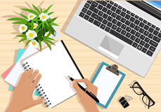 Top view of table with laptop, papers, tablet, flowers, eyeglasses and hands with pen. Modern graphic business workplace. Royalty Free Stock Photos