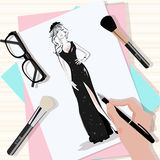Top view of the table with papers, hand drawn fashion woman in black dress, brushes, eyeglasses and hand with pen. Stock Photos