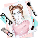 Top view of the table with papers, woman`s portrait, brush, lipstick, eyeglasses and eyeshadows. Stylish graphic set. Royalty Free Stock Photo