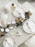 Top view of Table served for Xmas. Xmas dinner in living room. Plate with linen napkin, napkin holders, pine cones, wine glass Royalty Free Stock Photos