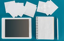 Top view of tablet with blank screen with blank papers and pen. On blue Royalty Free Stock Images