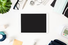 Tablet Computer With Medical Equipment On Table. Top view of tablet computer with blank screen and medical equipment on white table Stock Photography