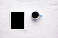 Top view of tablet computer and cup of coffee on wooden table Royalty Free Stock Photos