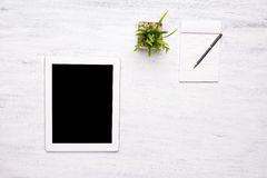 Top view of tablet computer and notepad on wooden table. Royalty Free Stock Image