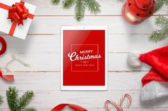 Top view of tablet with Merry Christmas message surrounded with Christmas decorations. Top view of white wooden desk Royalty Free Stock Images