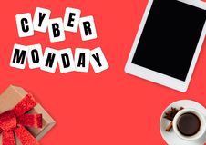 Top view of tablet and present, gift with cyber monday lettering on red background