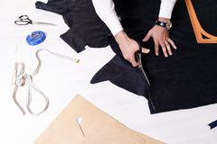 Tailor Cutting Fabric. Top view of tailors table with different tools, male hands cutting fabric on it making pattern for clothes Stock Photos