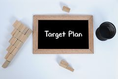 Top view of TARGET PLAN handwritten with white chalk on a blackboard.Pencil cup and Wood block stacking as step stair symbol of royalty free stock photo
