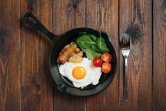 Top view of tasty bacon, egg, spinach and tomatoes with fry pan on the wooden table. royalty free stock photography